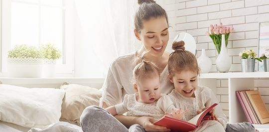 Mom reading a book to daughters - Danbury family law attorney